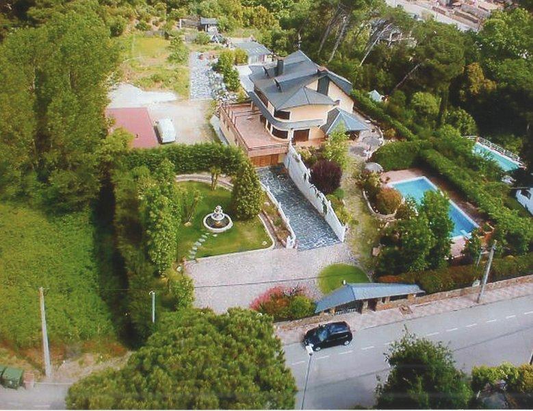 Vista aérea del alojamiento, con su piscina exterior, jardines, rampa hacia el parking y patio