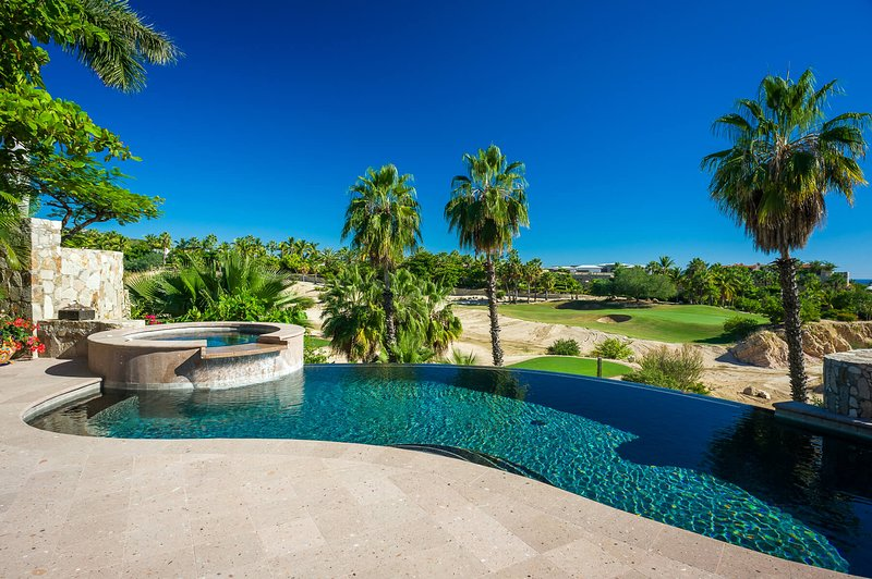 Surrounded by tall, leafy palms, the terrace of Entradas 64 includes a spacious pool and Jacuzzi