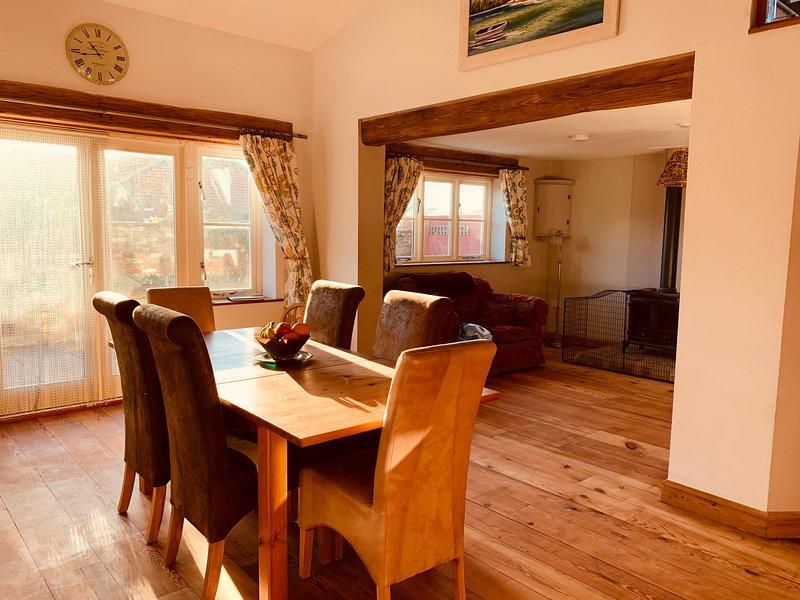 Sala de jantar de plano aberto, cozinha e sala de estar com lareira.