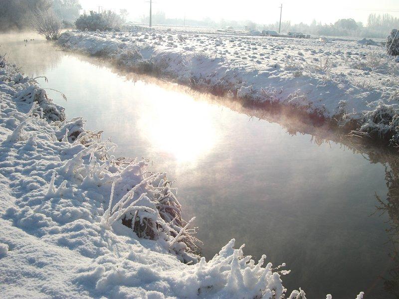Zicht op het huisje op de besneeuwde rivier