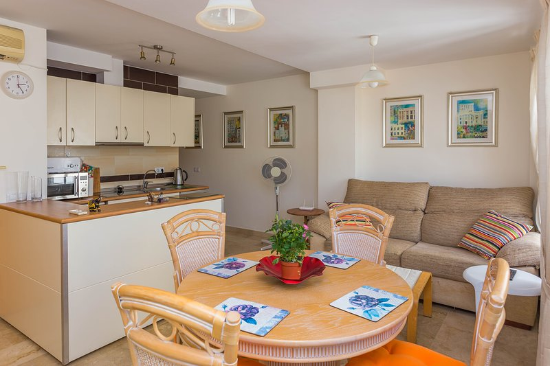 The living room has a dining table and a comfortable sofa with UK TV