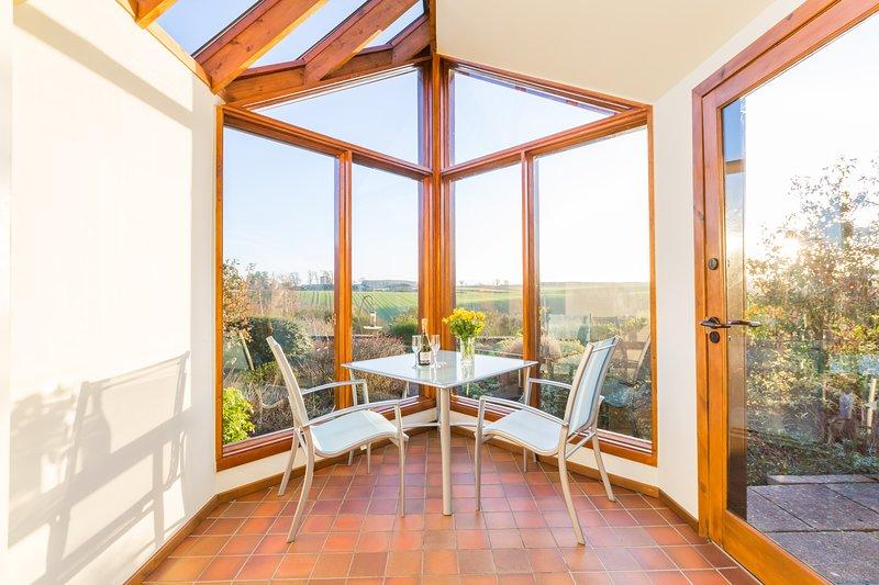 Relájese en su espacioso jardín de invierno mientras admira las vistas rurales del jardín de la casa de campo.