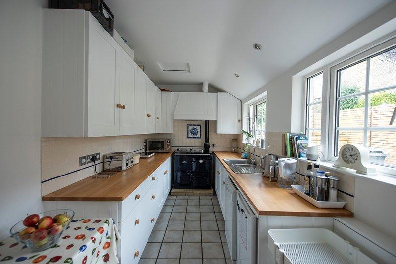 La cocina, con Rayburn, vitrocerámica, microondas, tostadora, hervidor, cafetera.