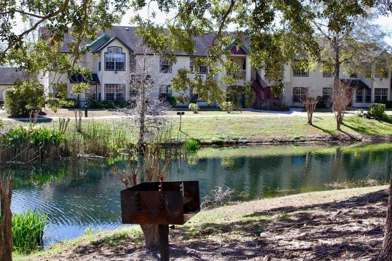 Superbe aménagement paysager, des arbres et un joli lac.