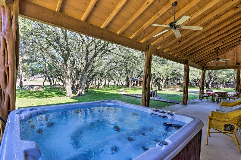 This Blanco home features a private hot tub, covered porch, and shared amenities