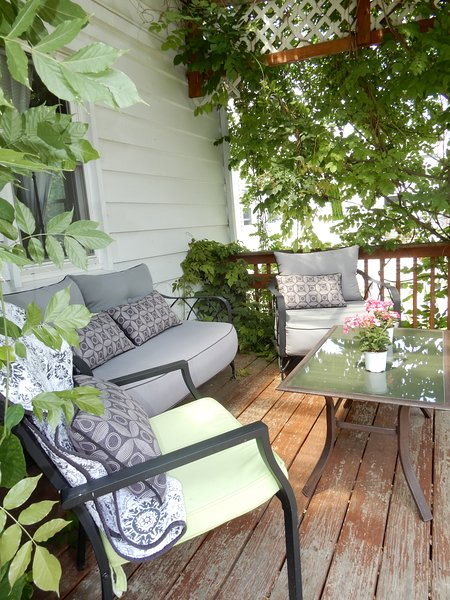 A covered deck, with cascading Wisteria, graces the back yard