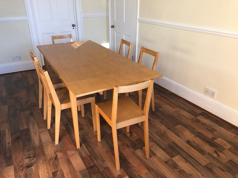 Dining table with 6 chairs is in the spacious kitchen.