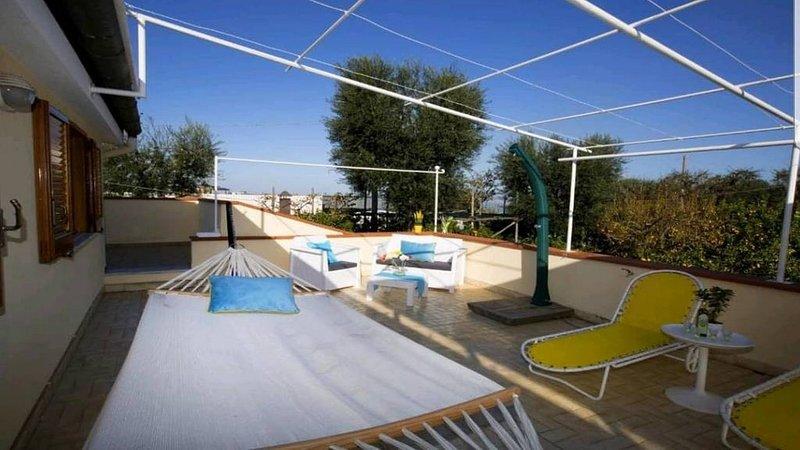 Outdoor large terrace with sofa, solarium and hammock sorrento casa mariandreA holiday booking villa