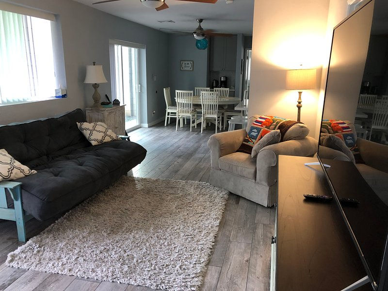 living room with queen futon and 65 inch smart tv