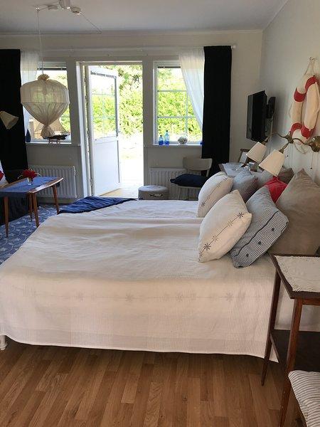 Les lits placés au milieu de la pièce. Porte au patio.