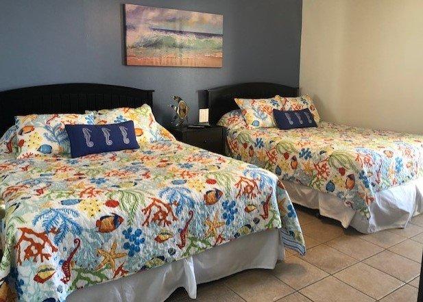 Come si entra nel condominio la camera da letto a destra ha due letti queen size con trapunte colorate e hanno 4 cuscini standard e anche un bagno di corridoio per gli ospiti.