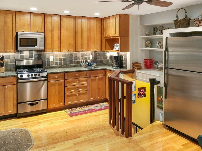 Fully stocked kitchen with stainless steel appliances, granite countertop, and slate backsplash