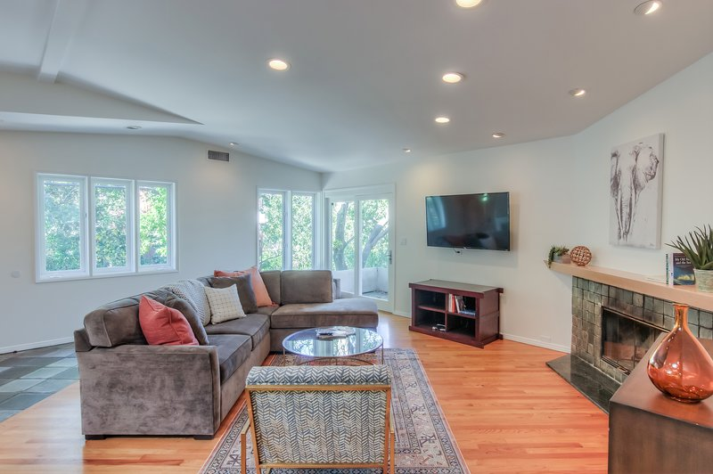 The bright and spacious living area features high ceilings, a decorative fireplace, 55' TV