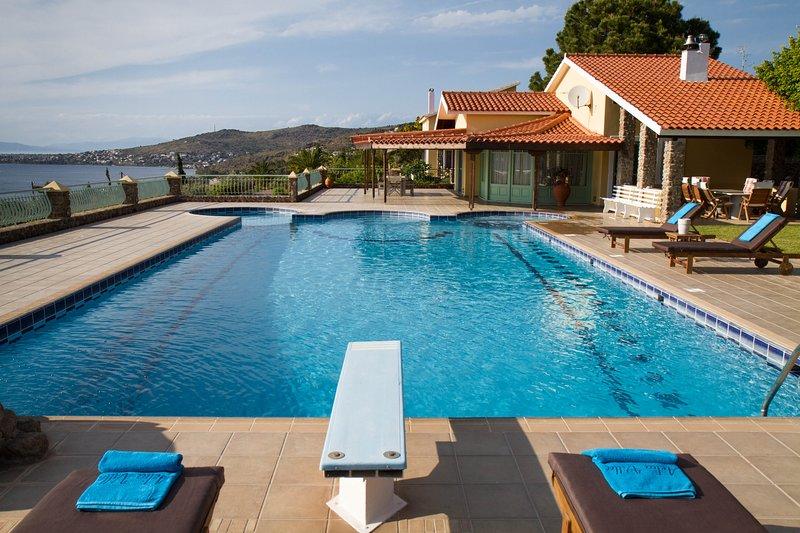 Extérieur de la villa avec piscine et coin salon