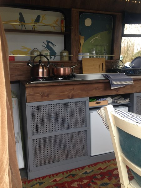 Fully equipped hand crafted kitchen area with 2 ring gas stove, belfast sink and fridge.