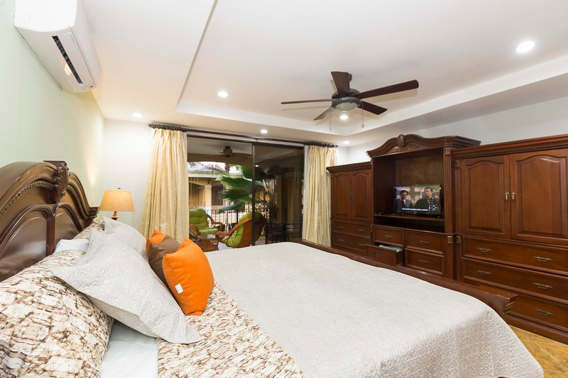 Master bedroom with king bed, tv, a/c, private bathroom and balcony