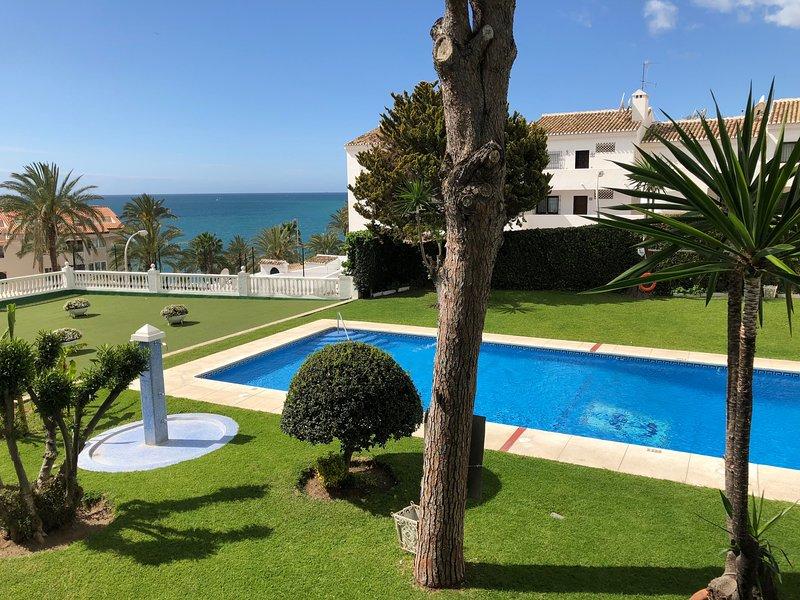 vista de jardin, piscina y mar desde el apartamento