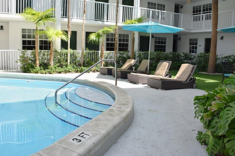 Large swimming pool with poolside loungers and umbrellas