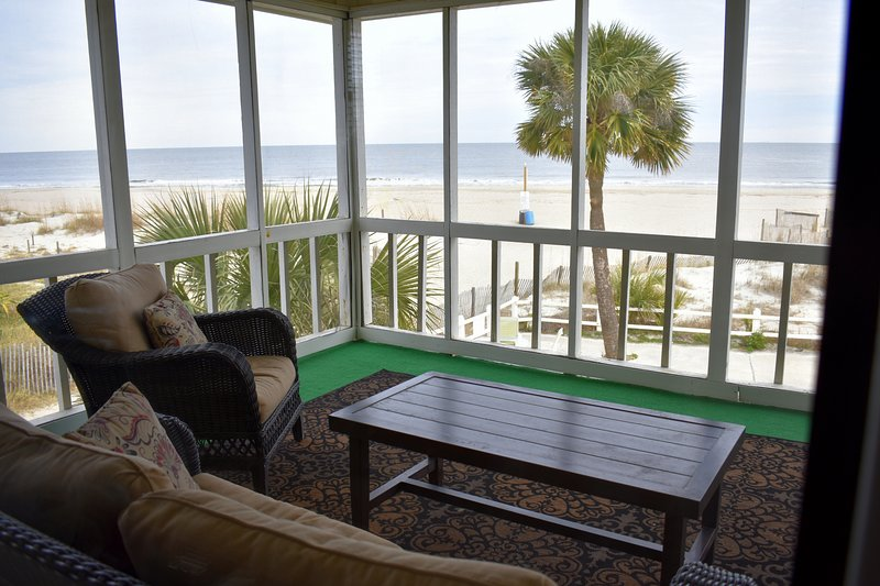 view of the ocean and screened porch seating area from the kitchen
