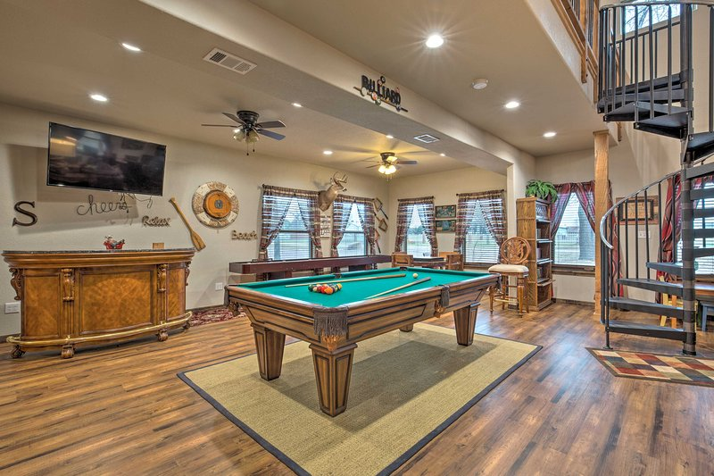 This 5-bed, 5.5-bath house showcases a game room and furnished wraparound porch