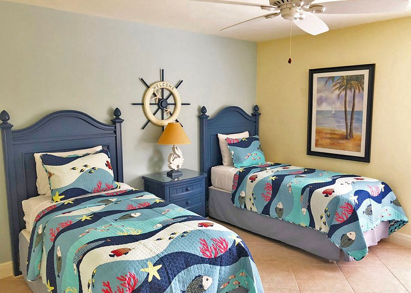 Seconda camera da letto con due letti singoli in una camera da letto a tema nautico con nuovi materassi e TV
