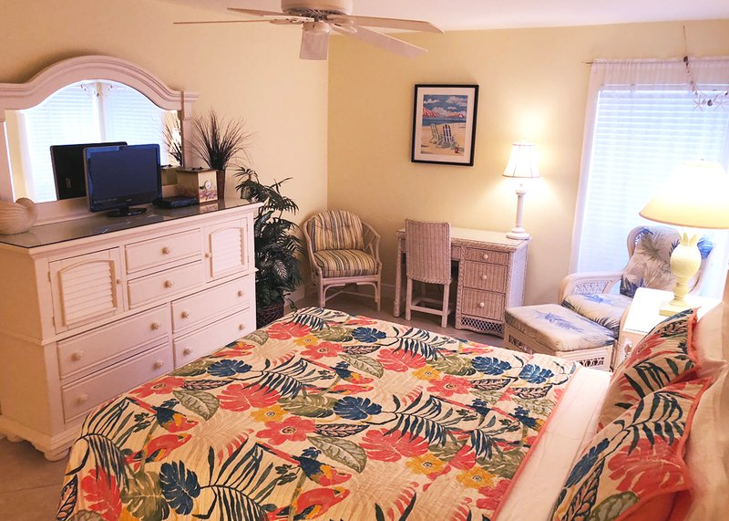3rd bedroom with a queen bed in a tropical floral themed bedroom with a new matress and TV
