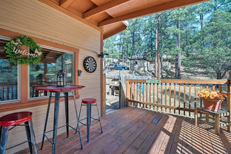 The home has an expansive deck with outdoor seating and a dart board.