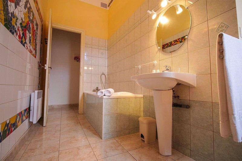 Baño con bañera, lavabo e inodoro.