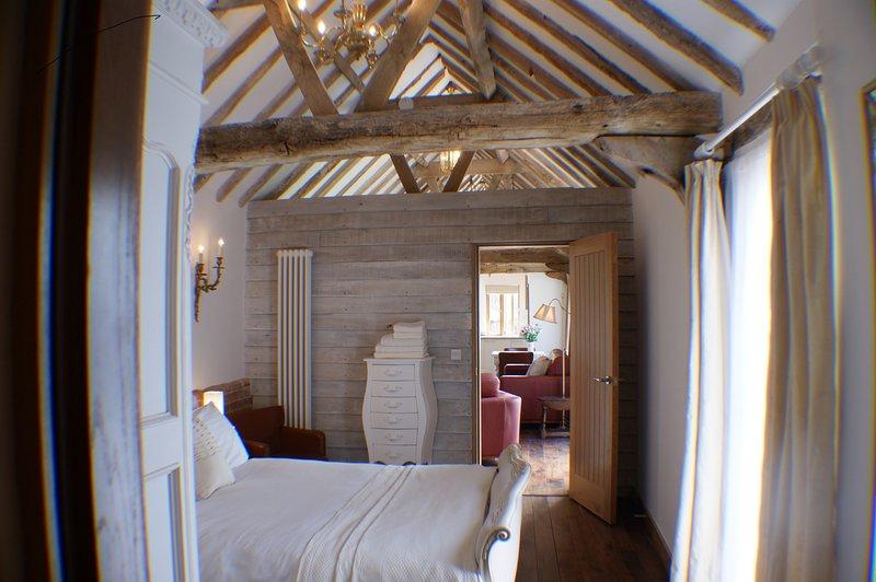 Schlafzimmer mit antikem französischen Bett. Baumwollbettwäsche, Bettwäsche, flauschige Handtücher und Toilettenartikel.