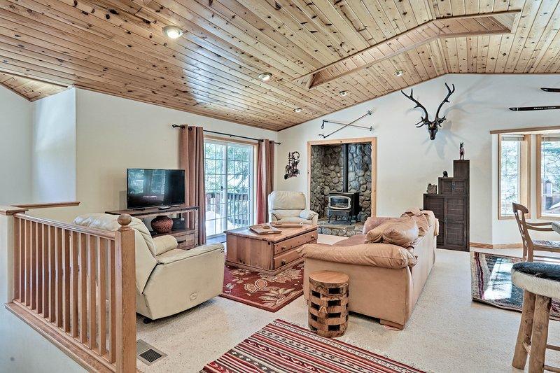 Esta cabaña de 2,000 pies cuadrados tiene acentos de pino nudoso y una estufa de leña.