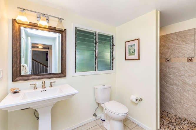 Cuarto de baño amplio a nivel del suelo con plato de ducha y suelo de piedra.