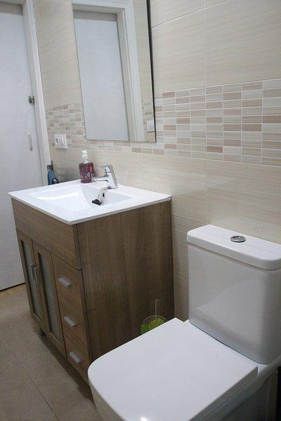Badezimmer mit Duschwanne komplett renoviert mit Handtüchern, Haartrockner, Gel und Shampoo.