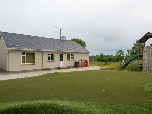Putting green and play area at the back of the property.