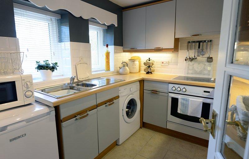 Cocina compacta y bien equipada con cocina eléctrica, lavadora y nevera.