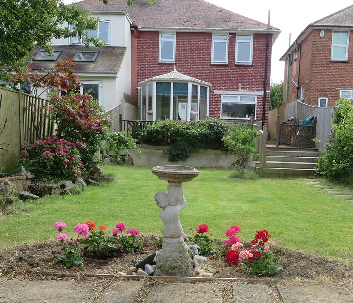 There is a large garden with a paved terrace and a boarded area perfect for outdoor meals.
