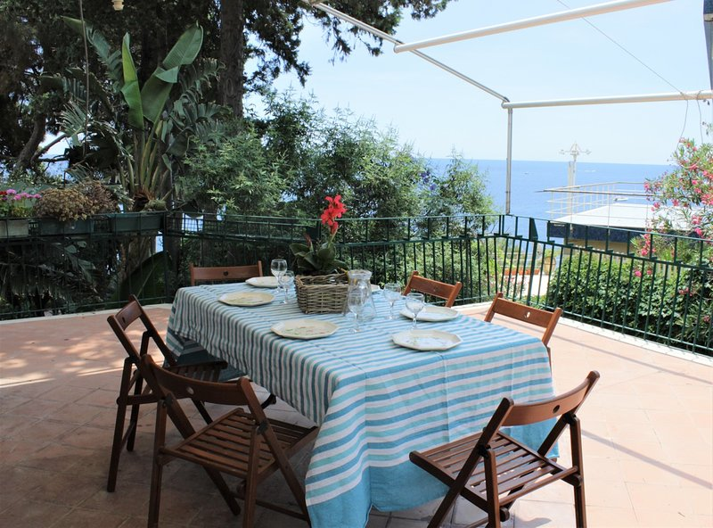 terraço com vista para o mar para os hóspedes, equipado com mesa, cadeiras e espreguiçadeiras