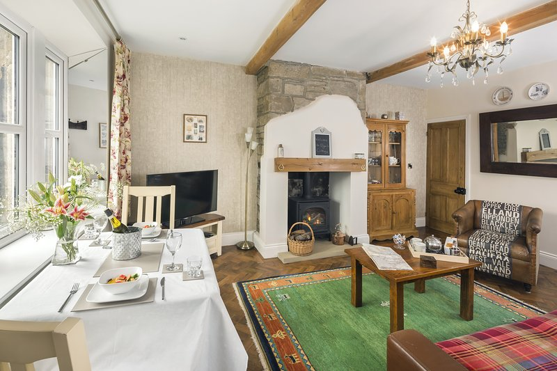 Relax in the spacious living room with high ceilings, ceiling beams and exposed stone fireplace