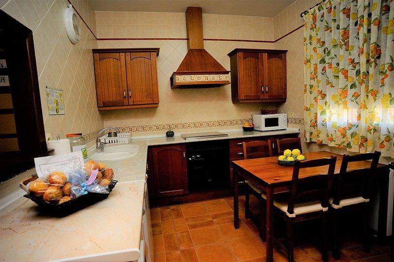 Voll ausgestattete Küche mit Utensilien und Geräten.