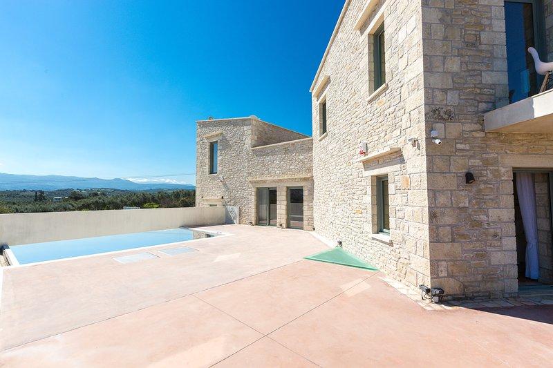 El área al aire libre de Villa Iasion cuenta con una piscina privada climatizada, barbacoa de gas y mesa de comedor.