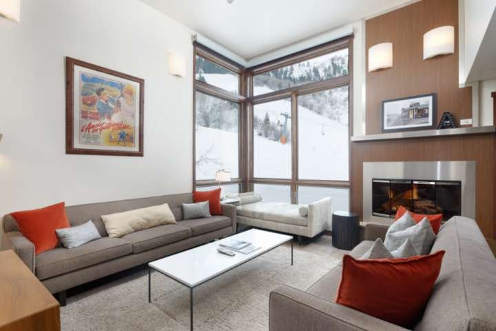 The warm and inviting living room features a gas fireplace, flat screen TV, plenty of seating and views of Aspen Mountain.