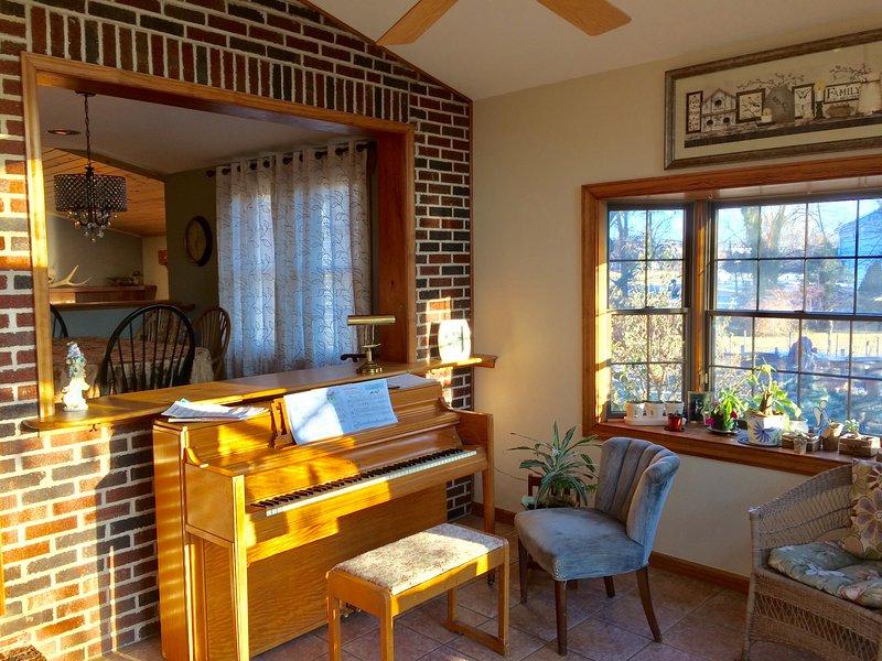 Veranda con vista sul giardino che si apre sul ponte e sul patio in pietra blu. Pianoforte per gli amanti della musica.