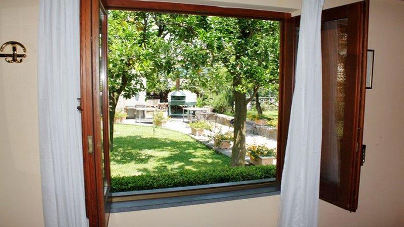 Vista al jardín desde el apartamento CasaGiordana con piscina compartida en el complejo de reservas de vacaciones.