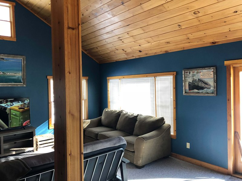 Living room with plenty of seating, blue tooth stereo, 55 inch smart TV with local channels and Hulu