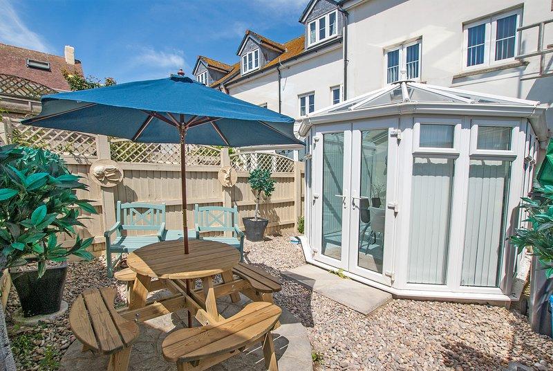 Patio de jardín trasero cerrado atractivo con función de centro, mesa, sillas y sombrilla.