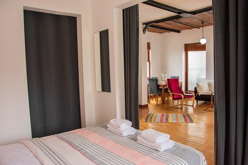 Cama king size con salón minimalista.
