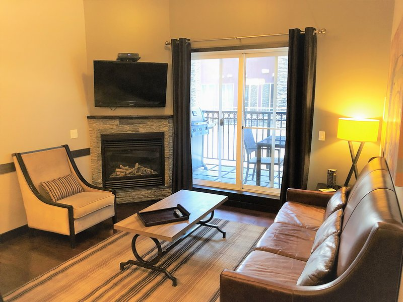 Spacious living room with cozy fireplace, flat screen TV,  and patio