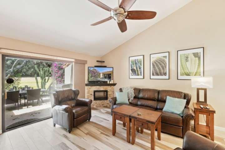 Ljust och öppet vardagsrum med plattskärms-TV och bekväma vilstolar.