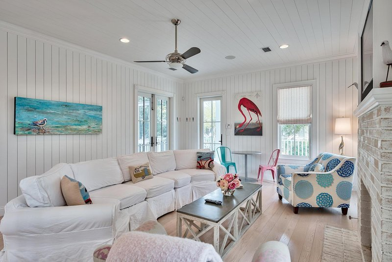 The living space features creamy whites, coastal blues and pops of coral