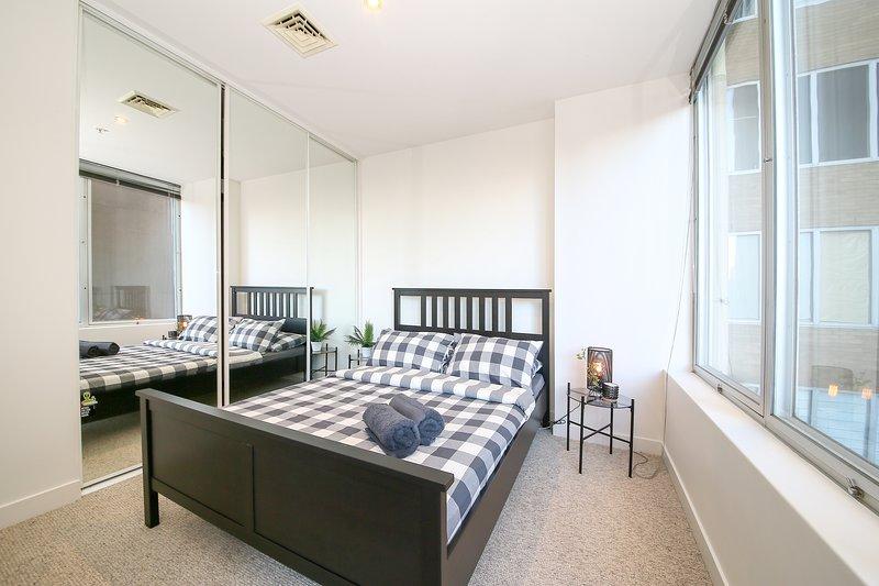 La chambre principale avec un lit queen size et des oreillers moelleux.