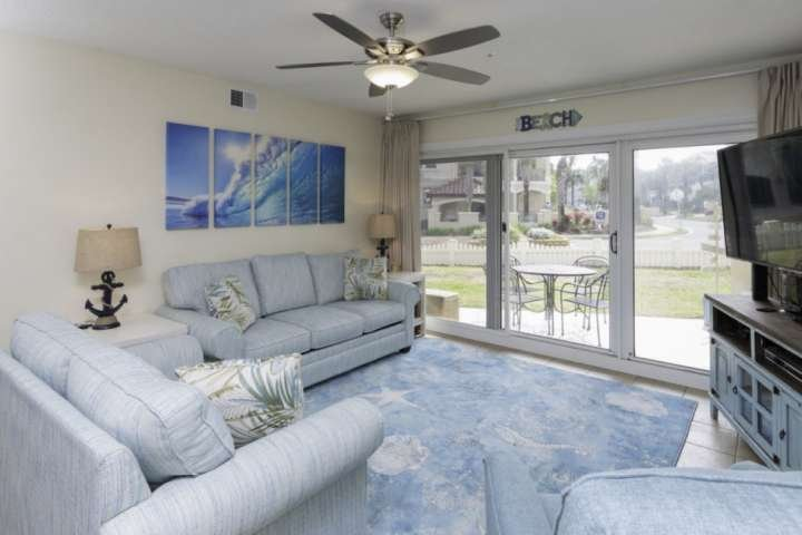 Living room with seating for 6, large flat screen TV, ceiling fan and access to patio